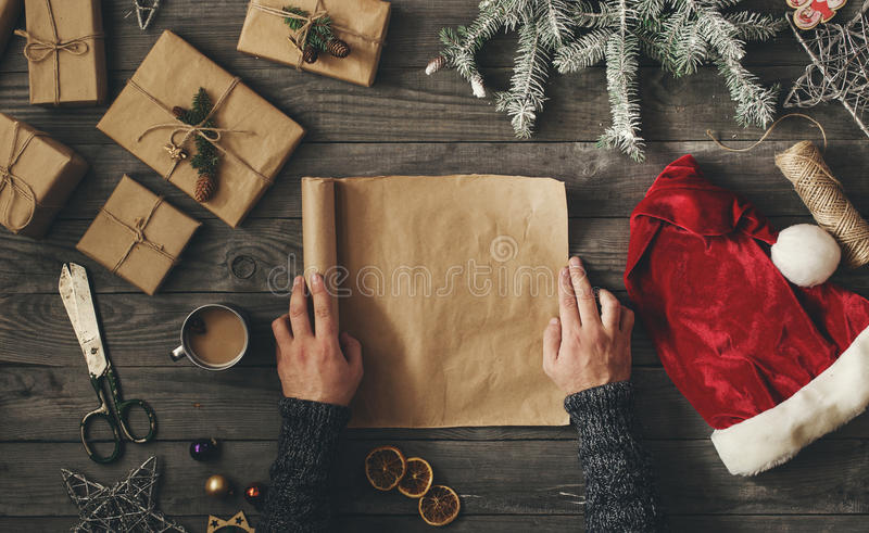 Men hands holding blank sheet of paper with Christmas gift. Men hands holds blank sheet of paper on dark wooden table with Christmas gift, overhead view stock images