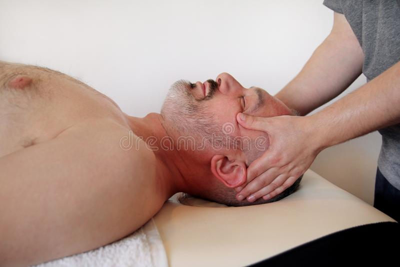 Men hands masseuse for massage the head of a guy. Massage studio. Men hands masseuse for massage the head of a guy. Body care. Man having massage in the spa body royalty free stock photo