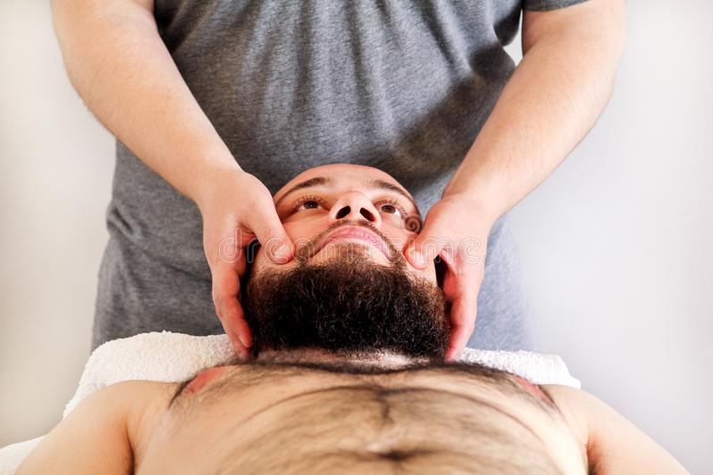 Men hands masseuse for massage the head of a guy. Massage studio. Men hands masseuse for massage the head of a guy. Body care. Man having massage in the spa body stock image