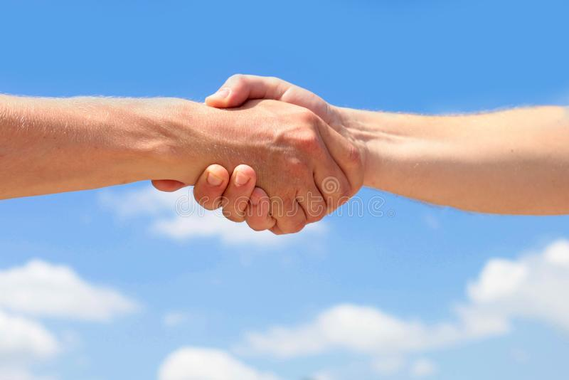 Men is handshake against the background of clouds and the blue sky. stock image