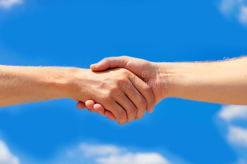 Men is handshake against the background of clouds and the blue sky. Copy spase royalty free stock images