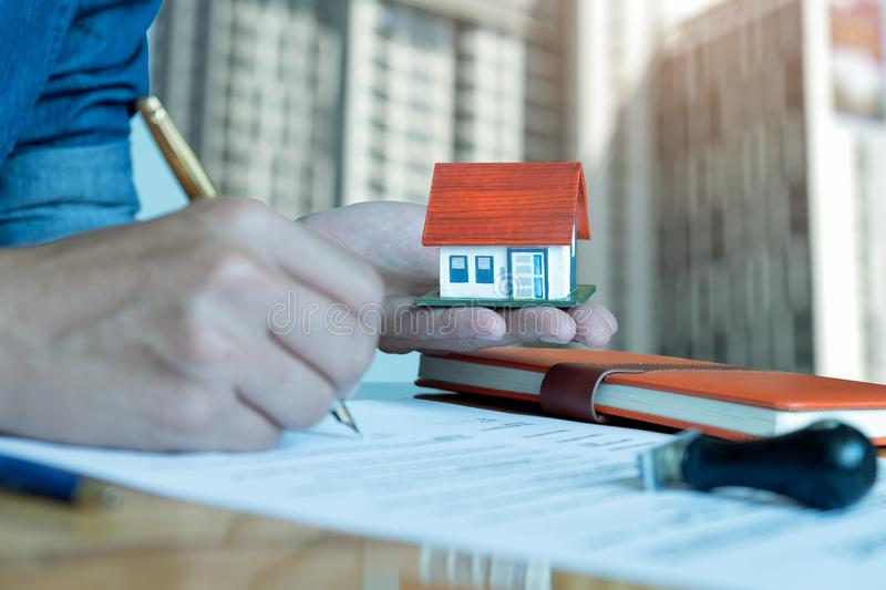 Men have a model house on hand,other hand is using a pen signing stock image