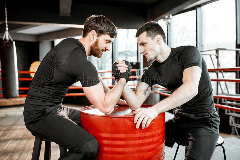 Men having arm wrestling in the gym. Two young athletes in black sportswear having a hard arm wrestling competition on a red barrel in the gym stock image