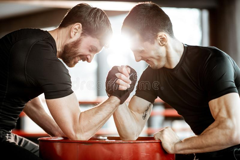 Men having arm wrestling in the gym. Two young athletes in black sportswear having a hard arm wrestling competition on a red barrel in the gym stock photography