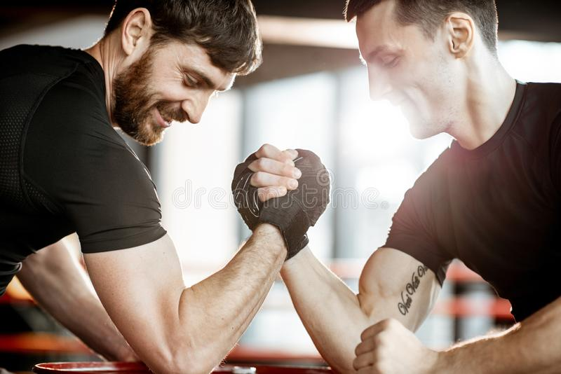 Men having arm wrestling in the gym. Two young athletes in black sportswear having a hard arm wrestling competition on a red barrel in the gym stock images