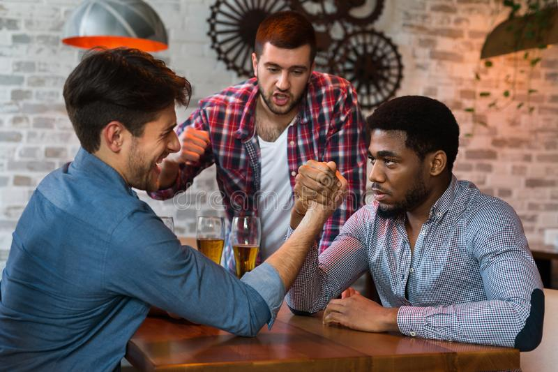 Men having fun, arm wrestling each other in bar. Men having fun, arm wrestling each other, drinking beer in bar royalty free stock images