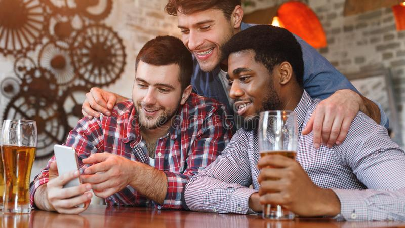 Men Having Fun. Friends Using Smartphone And Drinking Beer. In Bar stock photos