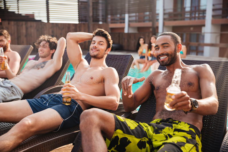 Men having fun in swimming pool and drinking beer. Handsome young smiling men having fun in swimming pool and drinking beer stock image
