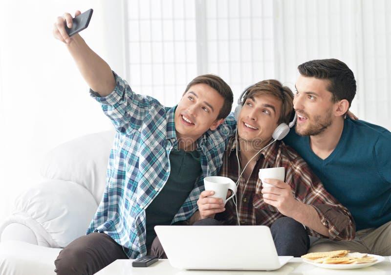 Men having fun taking selfie photo. Friendly men having fun taking selfie photo with smart phone at home royalty free stock image