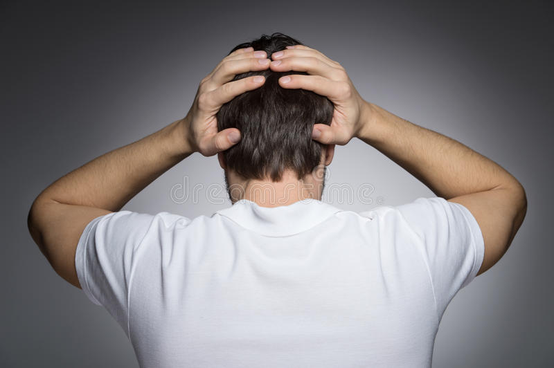 Men with headache. Rear view of men holding his head in hands while standing isolated on grey stock image