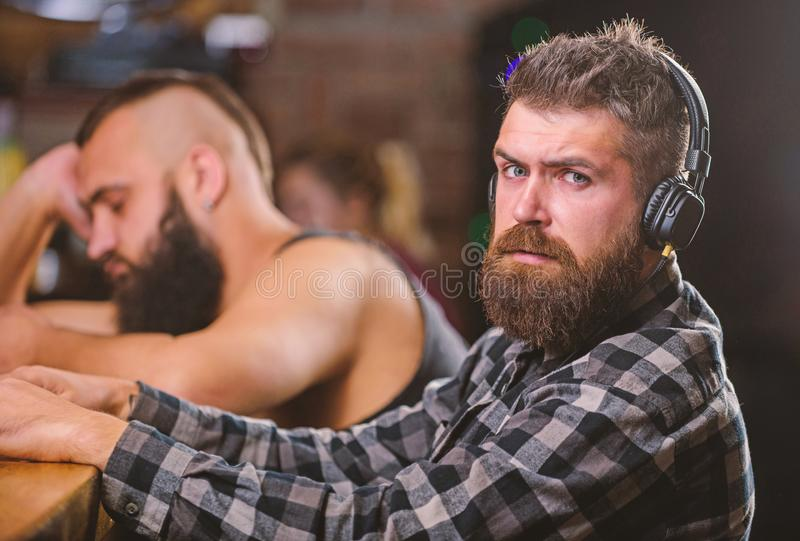 Men with headphones and smartphone relaxing at bar. Avoid communication. Escape reality. Friday relaxation in bar. Hipster bearded men spend leisure at bar royalty free stock images