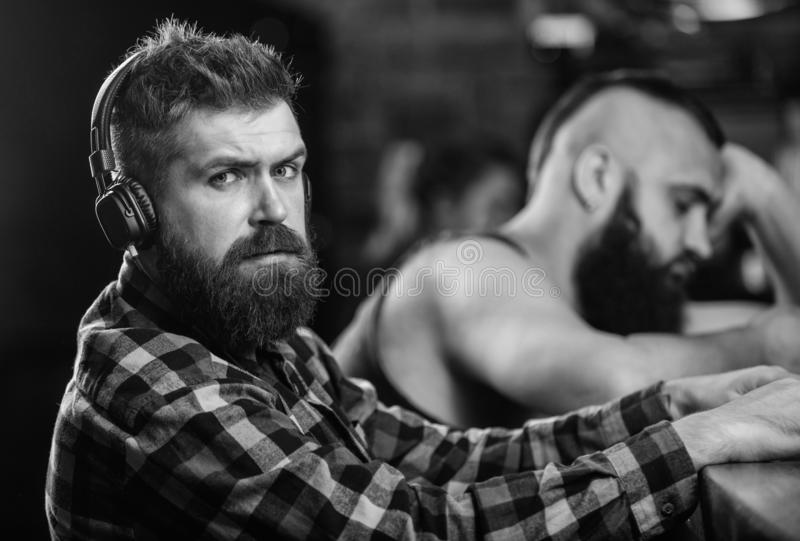 Men with headphones and smartphone relaxing at bar. Avoid communication. Escape reality. Friday relaxation in bar. Hipster bearded men spend leisure at bar royalty free stock photos