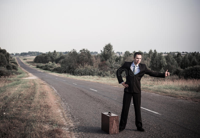 men hitchhiking on a road stock photos