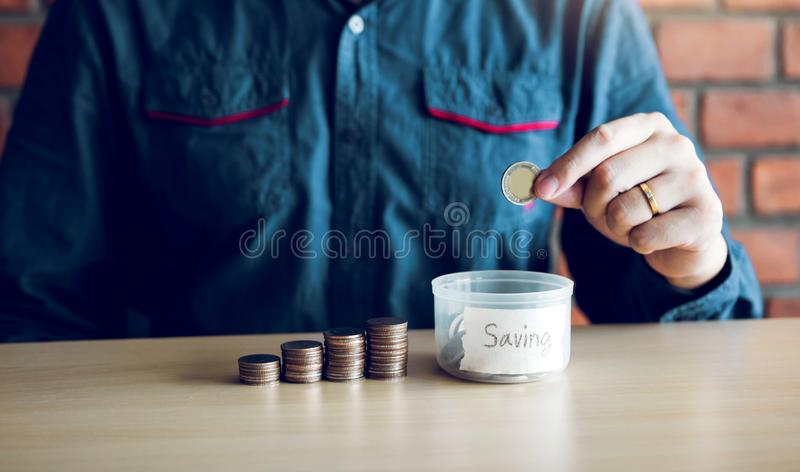 Men are holding coins dropping to the money box with the concept of saving stock images