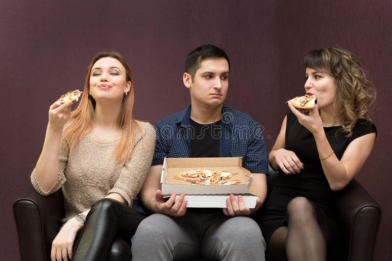 Man dieting looks like girlfriends eat pizza. A men because of illness can not eat pizza jealous girls stock photos