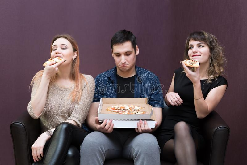Man dieting looks like girlfriends eat pizza. A men because of illness can not eat pizza jealous girls stock image