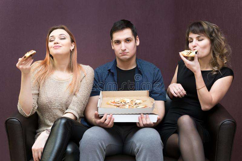 Man dieting looks like girlfriends eat pizza. A men because illness can not eat pizza jealous girls stock image