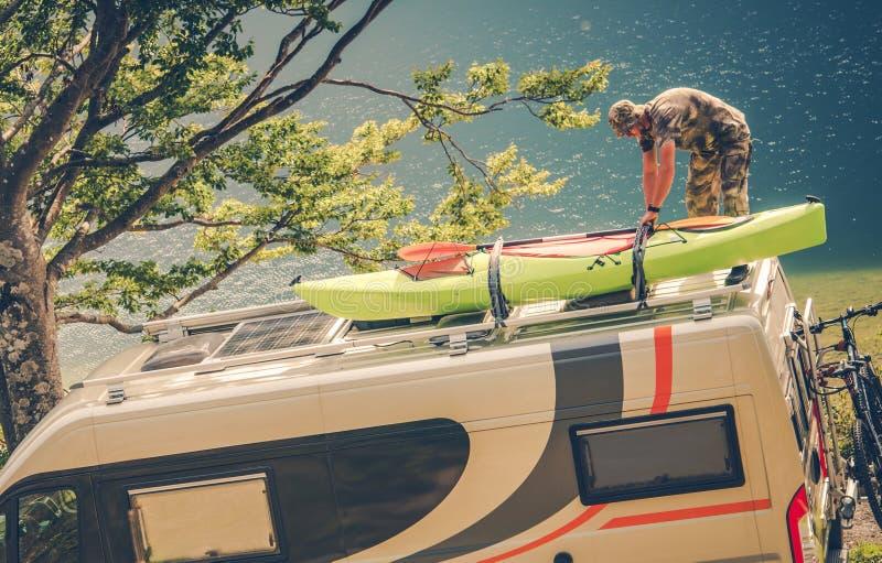 Men Installing Kayak on the RV. Camper Van. Preparing For the Next Motorhome Trip royalty free stock image
