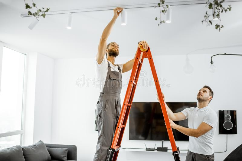 Men installing lights at home royalty free stock images
