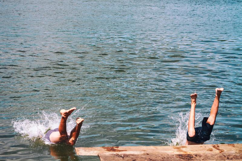 Men jumping off wooden pier, feet splashing on entry to water royalty free stock photography
