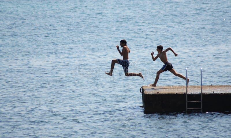 Men jumping in sea off pier stock photos