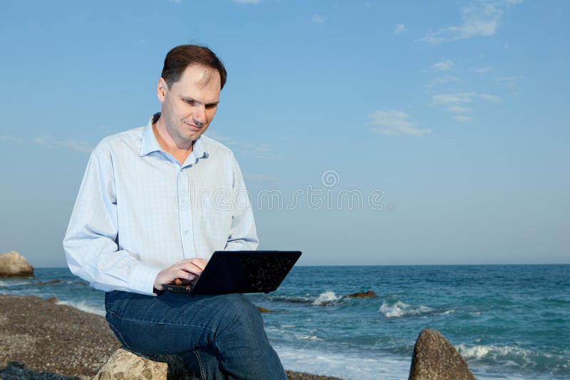 Men with laptop on the beach royalty free stock image