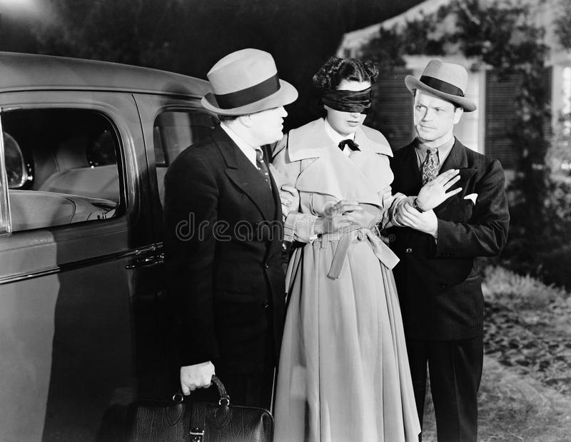 Men leading blindfolded woman royalty free stock photos
