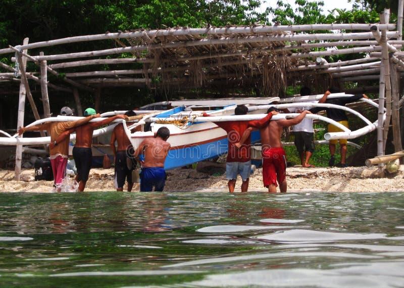 Men lifting boat to dock royalty free stock image