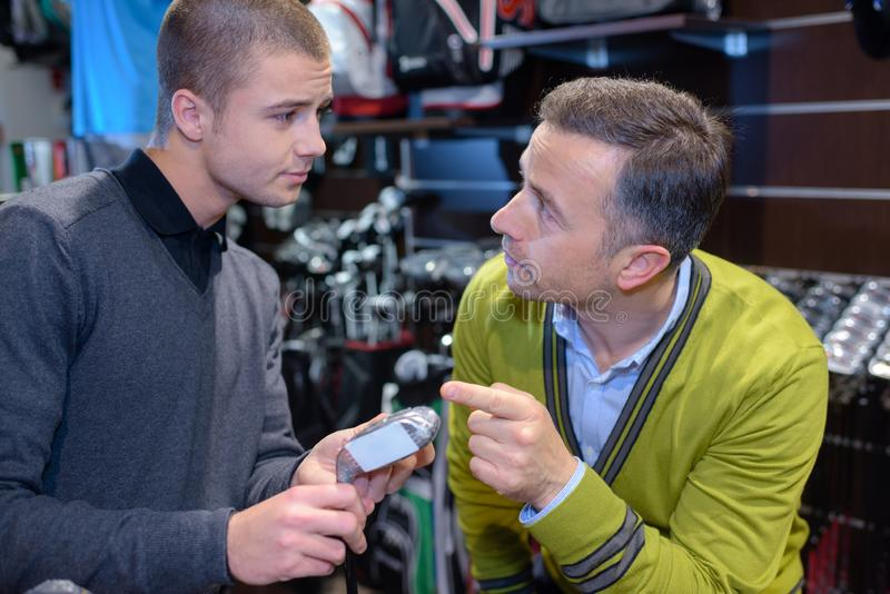 Men looking at golfing equipment. Golf royalty free stock photo