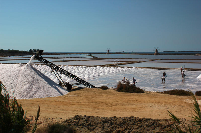Men and machines at saltpans in Mozia in Sicily stock images