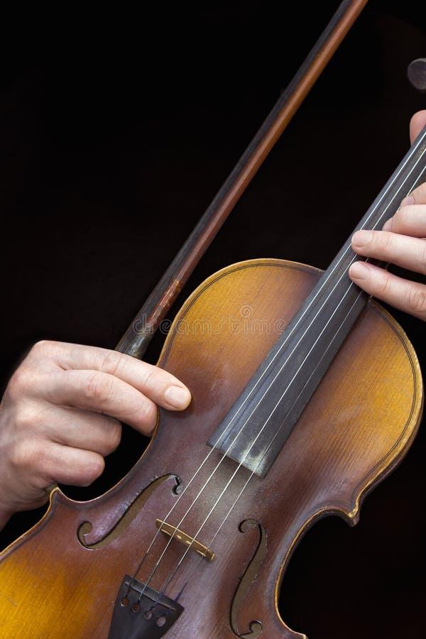 Men& x27 ; mains de s avec le vieux violon à un arrière-plan noir image libre de droits