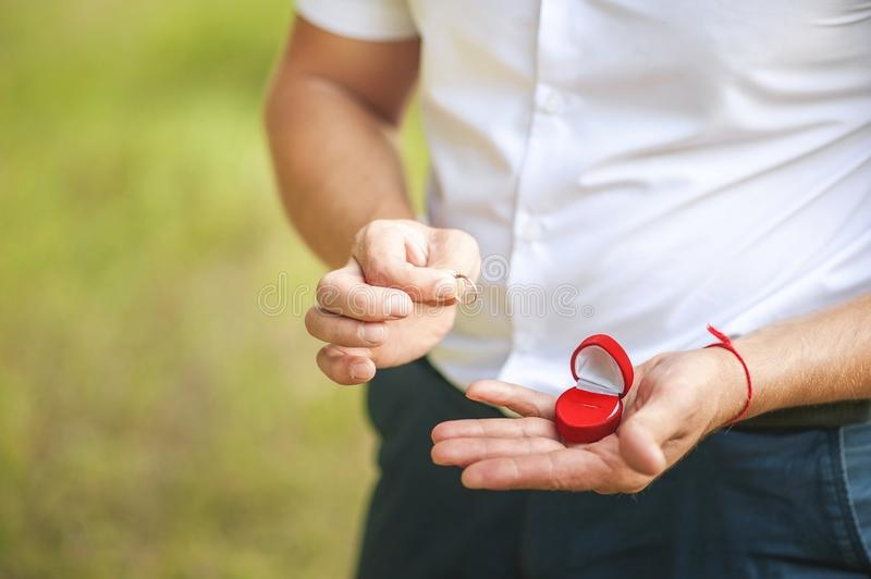 A man makes a proposal to beloved. Male hand holds wedding ring on the background of green nature. stock images