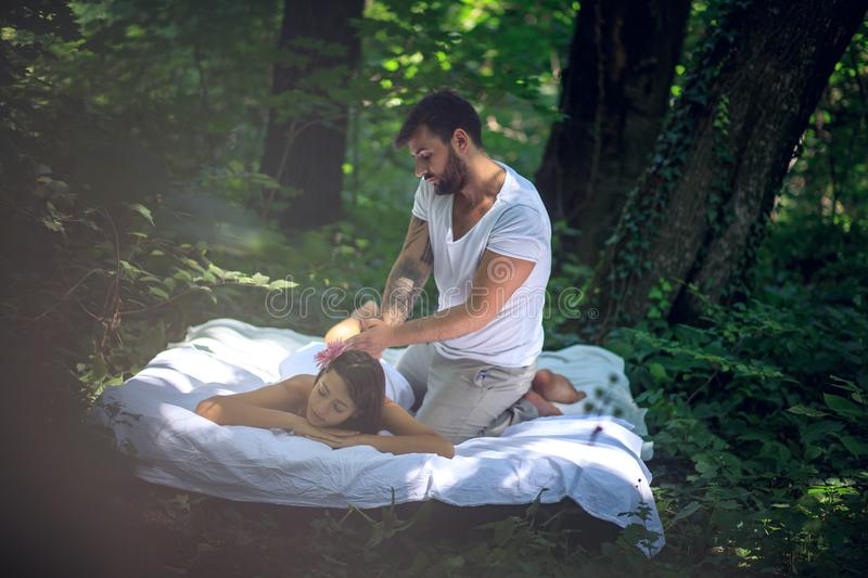 Men massage a women at nature. Spa treatment by my Men stock images