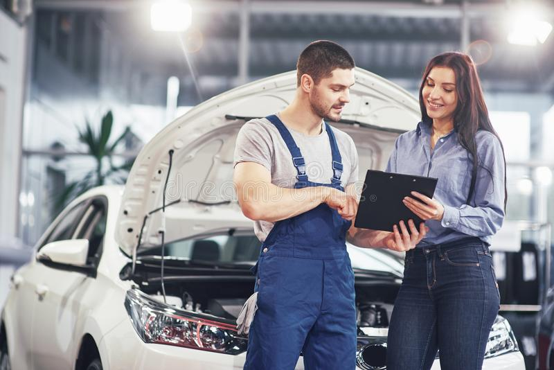 A man mechanic and woman customer discussing repairs done to her vehicle stock photo