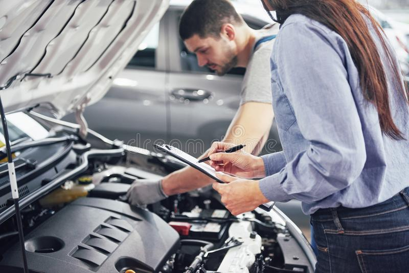 A man mechanic and woman customer look at the car hood and discuss repairs stock photo