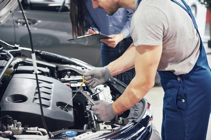 A man mechanic and woman customer look at the car hood and discuss repairs stock photos
