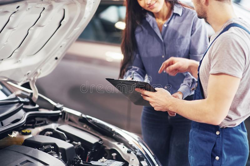 A man mechanic and woman customer look at the car hood and discuss repairs royalty free stock image