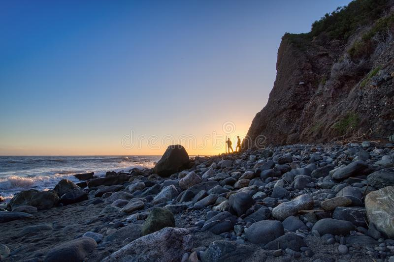 Men Near Dana Point Cliff at Sunset. Rocky shoreline view of two men standing near tall cliff at sunset with clear blue sky, Dana Point, California stock photo