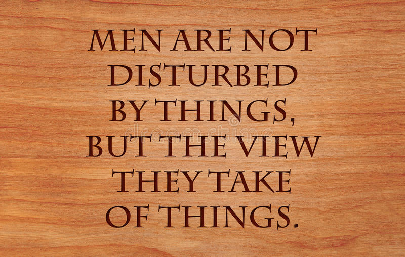 Men are not disturbed by things. But the view they take of things - quote by Epictetus on wooden red oak background royalty free stock photos