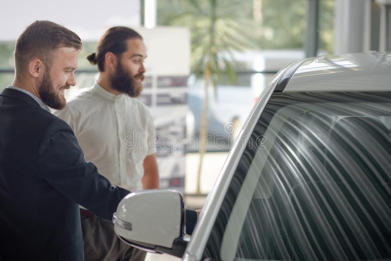 Men observing white auto in car center. E view of men observing vehicle in car center. Handsome bearded men smiling, looking at car. Windshield of white stock images