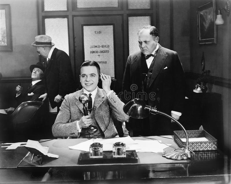 Men at an office one on the telephone. (All persons depicted are no longer living and no estate exists. Supplier grants that there will be no model release royalty free stock images