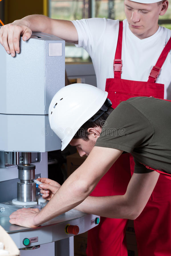 Men operating factory machine stock photos