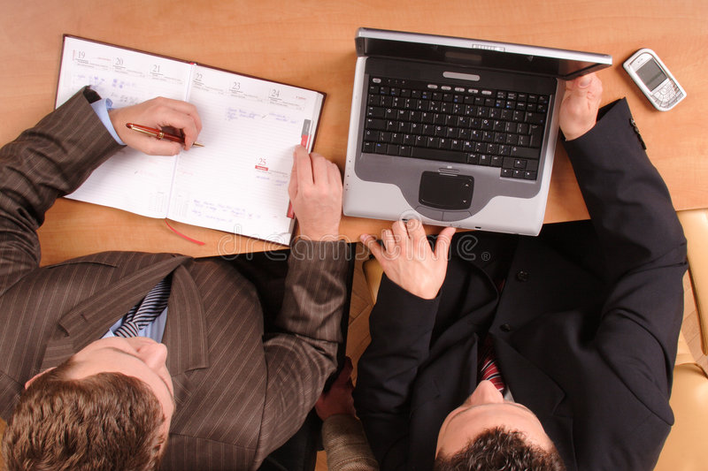 Men over the desk with laptop and calender on stock photos