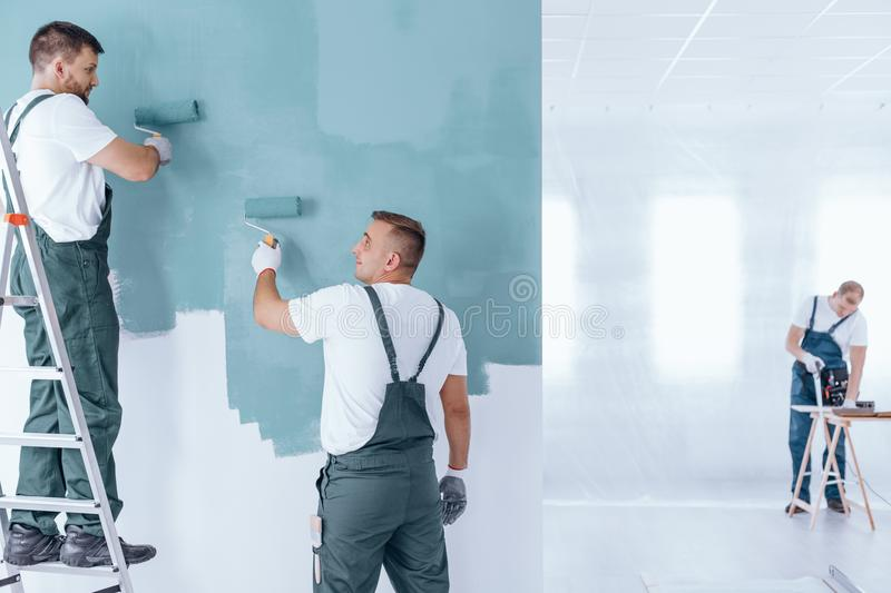 Men painting empty home interior. Men painting the wall blue using rollers in empty home interior stock images