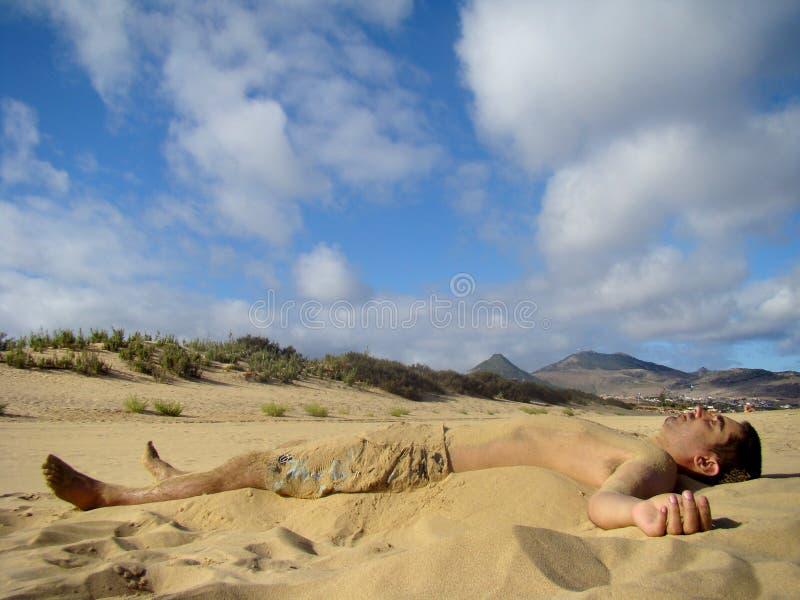 Men partial covered with sand having fun. In Porto Santo beach, Madeira Islands, Portugal stock photos