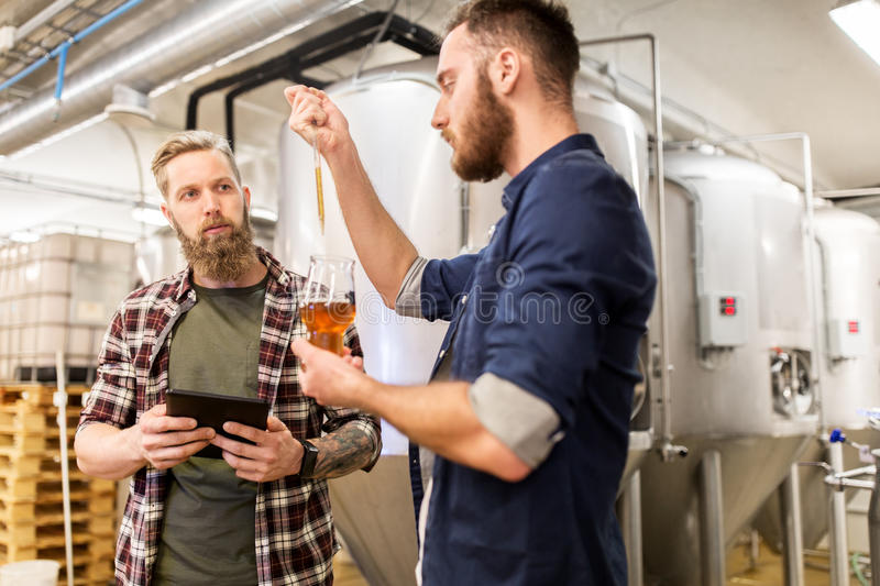 Men with pipette testing craft beer at brewery. Alcohol production, manufacture, business and people concept - men with pipette and tablet pc computer testing stock photography