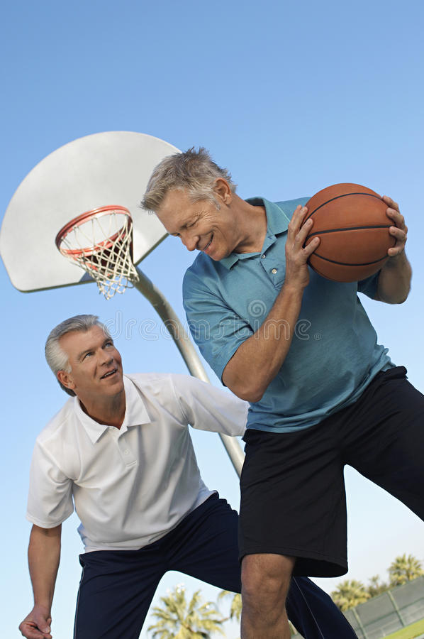Men Playing Basketball. Two male friends playing basketball at outdoor court royalty free stock image