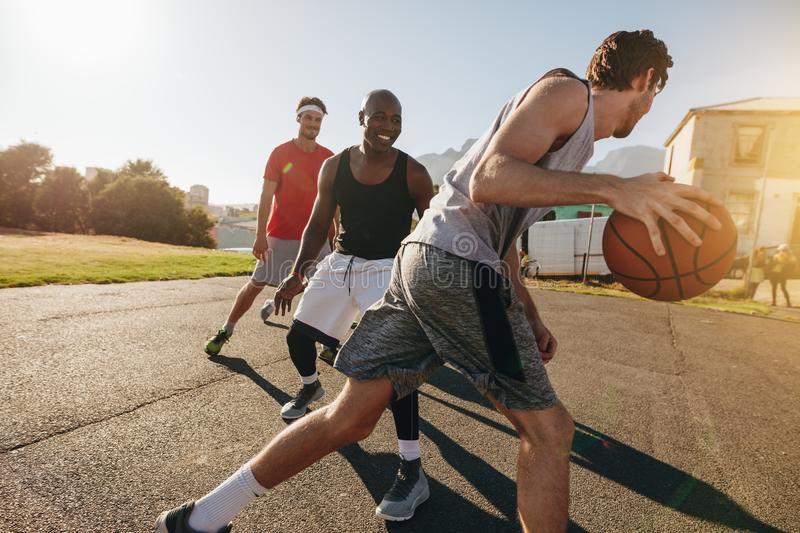 Men playing basketball. Game on a sunny day. Men practicing basketball skills in play area stock images