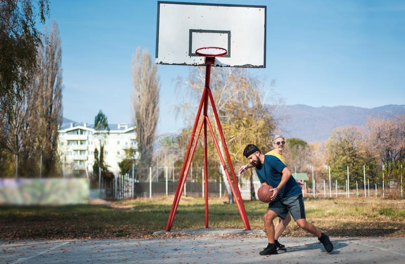 Men playing basketball in the park stock photo