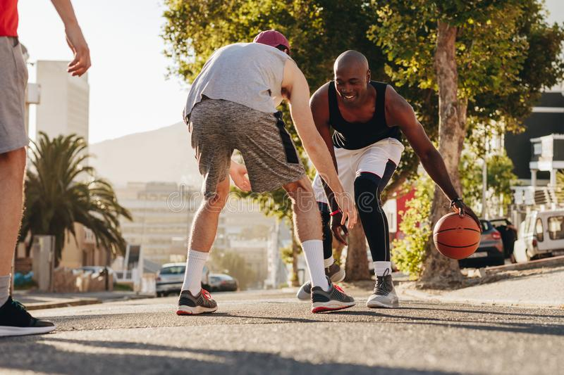 Men playing basketball on street. Men playing basketball game on a sunny day on an empty street. Men practicing basketball dribbling skills on street stock images